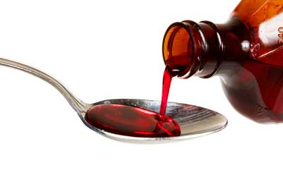 Photo of cough syrup being poured into a spoon