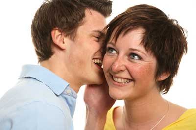 Photo of a man whispering into a woman's ear