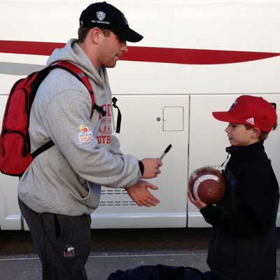 QB Jordan Lynch autographs a football for young fan Cole Heinisch.