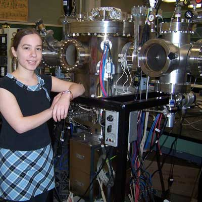 Gabriela Arriaga stands with an ultra-high vacuum (UHV) thin film deposition system.
