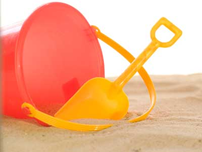 Photo of red plastic bucket and yellow scoop on sandy beach