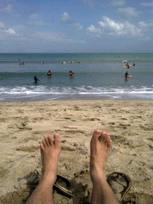 A photo of bare feet on a sandy beach on the ocean