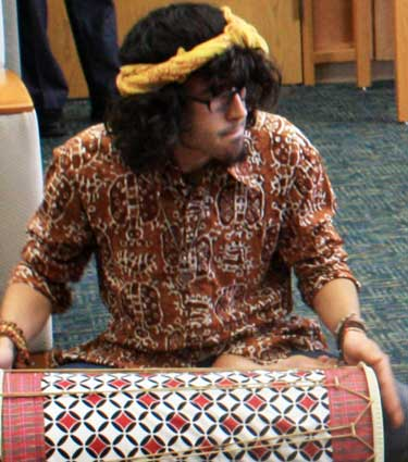 "A member of the NIU Gamelan Ensemble helps to break the ""quiet"" rule inside the Rare Books Room of Founders Memorial Library."