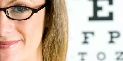Photo of a woman in glasses next to a eye chart