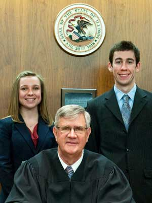 Second-year NIU Law students Amanda Wielgus and Anthony Gough stand with Chief Judge Michael P. McCuskey of the United States District Court for the Central District of Illinois.
