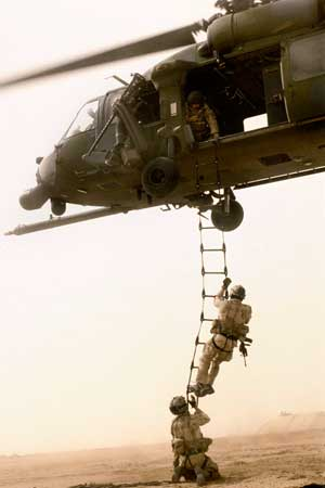 Photo of troops climbing the ladder to a helicopter