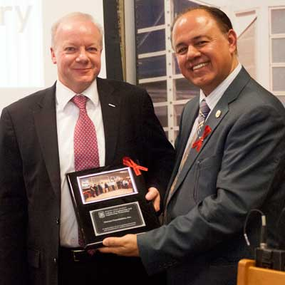 Promod Vohra, dean of the College of Engineering and Engineering Technology, celebrates with Nigel Blakeway, Omron CEO and president of the Omron Foundation.