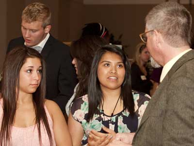 Students talk to Michael Day, director of the First Year Composition Program, at a previous Showcase of Student Writing.