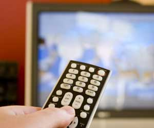 Photo of a hand pointing a remote control toward a TV