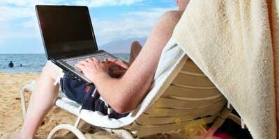 Photo of a man using a laptop on a beach