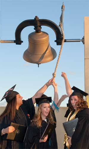 New NIU grads ring the bell outside the Convocation Center.