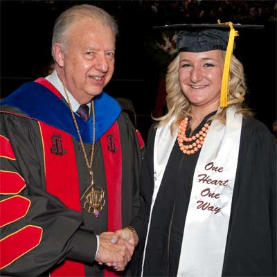 Peters shakes hands with Grace Reynolds after she received her diploma May 11, 2013.
