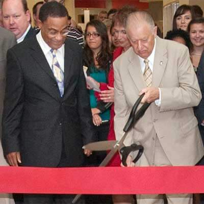 President John Peters, flanked by Executive Vice President and Chief of Operations Eddie R. Williams, cuts the ribbon for New Residence Hall.
