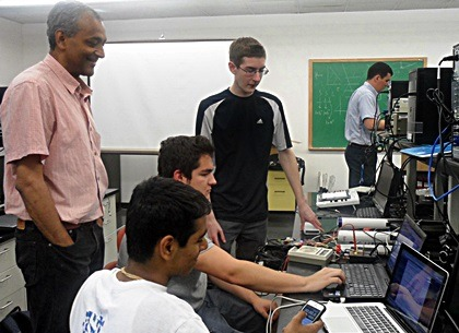NIU physicist Dhiman Chakraborty observes the students' progress in setting up their cosmic ray detector.