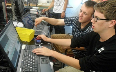 Neuqua Valley High School seniors Anders Nelson (left) and Jackson Davis (right) discuss readings recorded by their cosmic ray detector.
