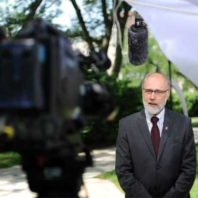 New NIU President Doug Baker films a video welcome message Thursday.