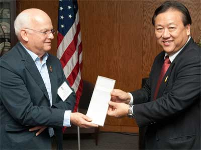 Welcome gift: Thai language professor John Hartmann accepts a grant for a Thai e-learning program from Thai Ambassador to the United States Chaiyong Satjipanon at a luncheon hosted by the Division of International Programs.