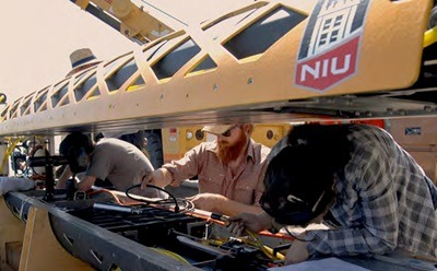NIU Ph.D. student Tim Hodson works with DOER engineers preparing the robotic submarine instrumentation for testing.