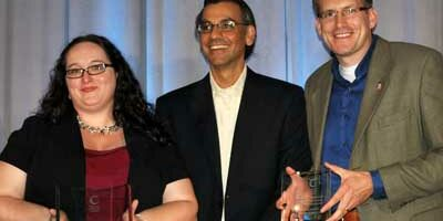 NIU's Stephanie Richter and Jason Rhode (right) accept awards alongside Jay Bhatt, president and CEO of Blackboard, Inc.