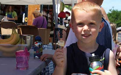 A young visitor to the Harvest Market prepares to enjoy a fruit kabob.