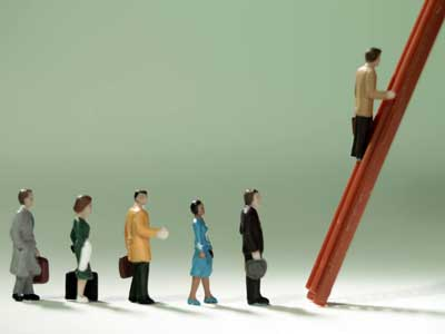 "Photo of  toy figurines of ""business people"" climbing the corporate ladder."