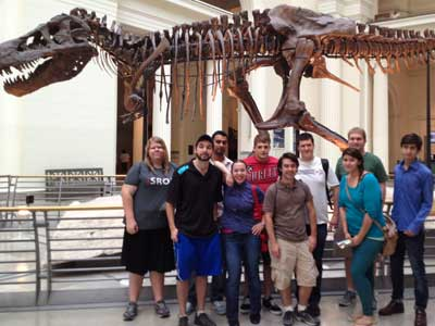 Students pose in front of the Field Museum's Tyrannosaurus Rex, Sue.