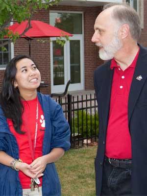 NIU President Doug Baker chats with a student outside Gilbert Hall.