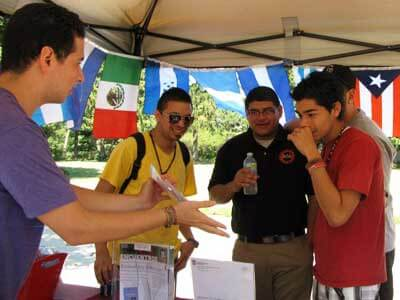 Southeast Asia's 11 country flags decorate the Center for Southeast Asian Studies at last year's annual Area Studies Open House while Victor Mendoza, left, graduate assistant for the Center for Latino and Latin American Studies (CLLAS), runs a Guess the Flags of Latin America game at the CLLAS tent.