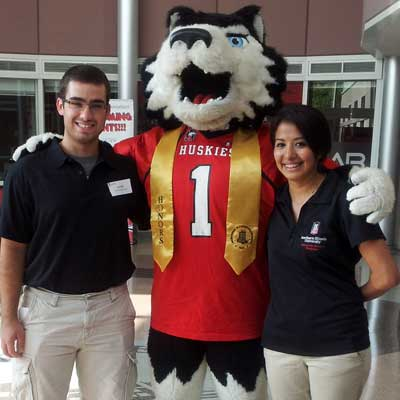 University Fellows Jarrett Wolske and Noemi Rodriguez join Victor E. Huskie, decked out in his Honors Program sash.