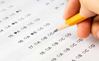Photo of a person taking a standardized test with a No. 2 pencil