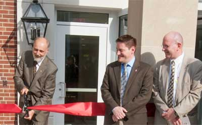NIU President Doug Baker cuts the ribbon Thursday at Gilbert Hall while Board of Trustees Chair John Butler (center) and former chair Marc Strauss (right) look on.