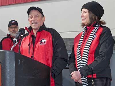 Kenneth and Ellen Chessick address the crowd gathered at the Yordon Family Huskie Pride Plaza, located on the east side of the Chessick Practice Center.