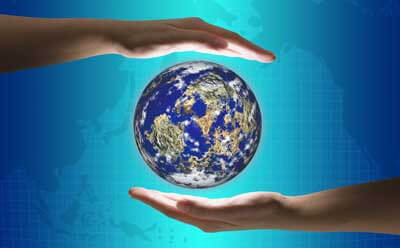 Image of hands framing the globe in front of a world map