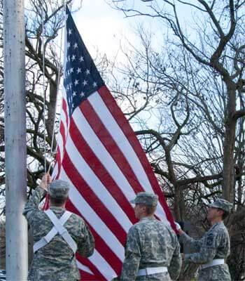 NIU ROTC members lower the flag at the 2012 Veterans Day's service.