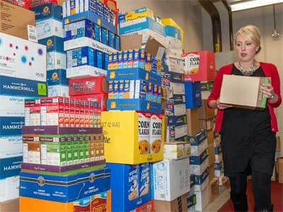 Jill Hayes, director of the Business Passport Program, checks out the mountain of non-perishables ready for donation to the food bank.