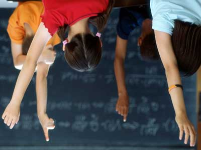 An upside-down photo of children raising their hands in a classroom.