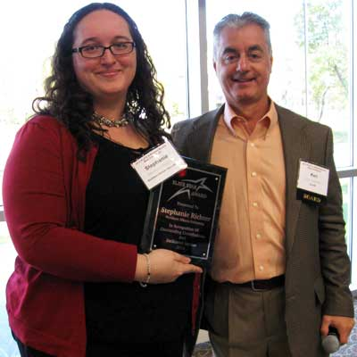 Stephanie Richter accepts her SLATE Star Award from Ken Sadowski, the organization's executive director.