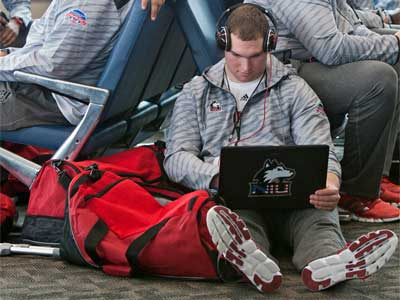 Tight end Kevin Tennenbaum works on his laptop while waiting for the team's flight at the Chicago Rockford International Airport.