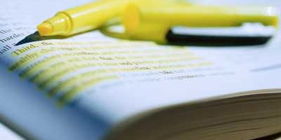Photo of a yellow highlighter on an open text book