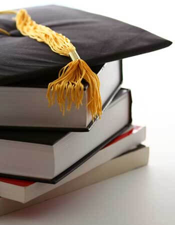Photo of a mortar board and tassel on a stack of books