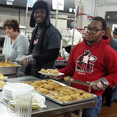 Huskie Service Scholars Blexendi Vixama and Keelan Wright dish up hot meals to the community at Feed'em Soup.