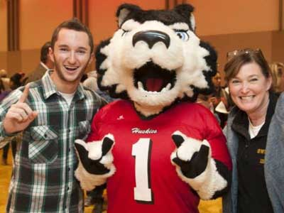 Victor E. Huskie greets an admitted student and his mother.