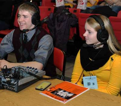 Sycamore High School student Jordyn Shultz (right) works at the broadcast table alongside DeKalb High School student Owen Smith.