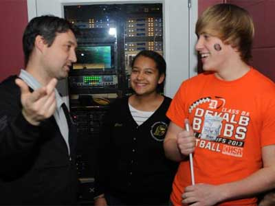 NIU's Patrick Gorman (left) explains Convocation Center control room operations to Emani Brinkman and DeKalb High School student Matt Petersen.
