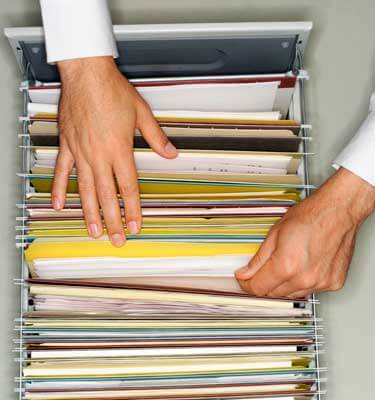 Photo of hands pawing through files in a cabinet