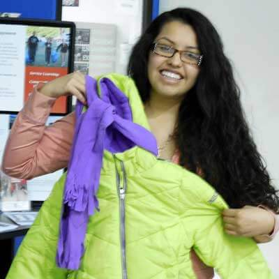 Huskie Service Scholar Shareny Mota sorts coats for Homelessness and Hunger Week.