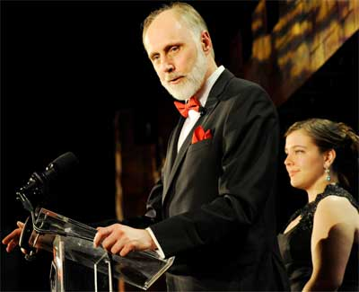 NIU President Doug Baker speaks at the Red and Black Gala while NIU Student Lincoln Laureate Sarah Stuebing listens.