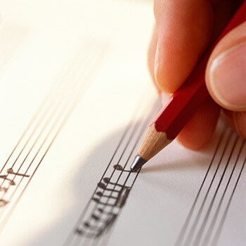 Photo of a hand and pencil writing musical notes on a staff