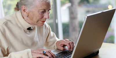 Photo of an elderly woman with a laptop