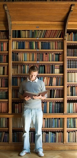 Photo of a man reading a book in front of a library shelf
